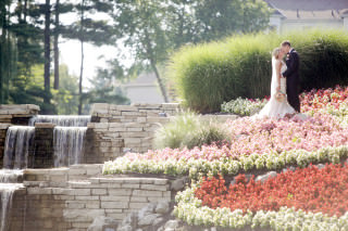 The happily married couple share a kiss by the waterfall at the lakes golf and country club in westerville.